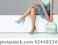 legs woman wearing high heels shoes sitting on bench. 42448334
