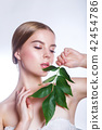 Beautiful woman face portrait with green leaf concept for skin care or organic cosmetics. Studio 42454786
