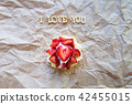 Bright cupcake with strawberries lies on craft paper, the inscription I love you 42455015