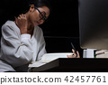 Girl in white shirt reading many textbooks table 42457761