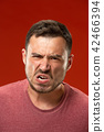 The young emotional angry man screaming on red studio background 42466394