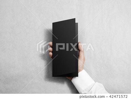 Hand holding blank black opened brochure booklet. 42471572