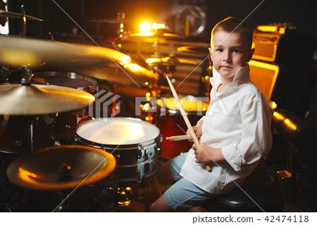 boy plays drums in recording studio 42474118