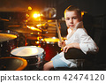 boy plays drums in recording studio 42474120