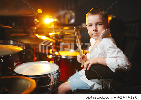 boy plays drums in recording studio 42474120