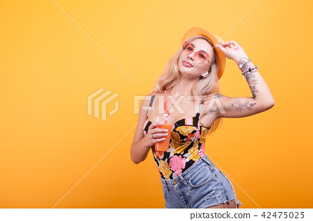 beautiful young woman with glasses holding fresh orange juice 42475025