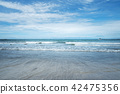 wave of the sea on sand and blue sky background.  42475356