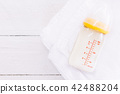 Baby bottle with milk on towel on wooden table 42488204