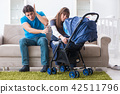 Young parents with their newborn baby in baby pram sitting on the sofa  42511796