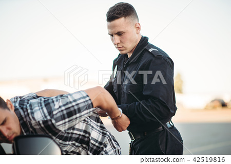 Policeman arrests the car thief on road 42519816