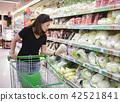 Young asian woman with shopping cart choosing prod 42521841