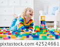 Child playing with toy blocks. Toys for kids. 42524661