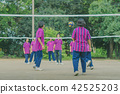 group of teenage friends playing volleyball  42525203