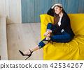 Young woman sitting on yellow sofa 42534267