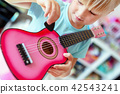 Little cute blond girl having fun learning to play small ukulele guitar at home.Toddler girl trying 42543241