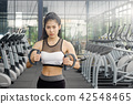 Beautiful woman exercise cable machine in gym. 42548465