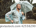 Attractive man strolling in rain 42556290
