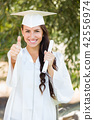 Mixed Race Thumbs Up Girl Celebrating Graduation Outside In Cap 42556974