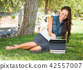 Happy Mixed Race Young Female Student With Books Using Computer 42557007