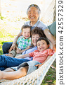 Chinese Grandparents In Hammock with Mix Race Boy 42557329