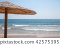 Tall umbrella standing in the sand. A wooden 42575395
