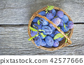 Plums in a wicker basket on the wooden background 42577666