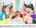 Cheerful woman holding a gift box during a surprise birthday party 42578252