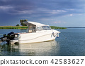 Luxury fishing motor boat moored at coast in bay on river or lake. Dark stormy sky with thunder 42583627