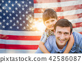 Father with Son Piggy Back Riding In Front of American Flag 42586087