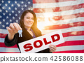 Hispanic Woman House Keys and Sold Sign In Front of American Fla 42586088