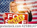 Young Woman Holds House Keys and Sold Sign by Flag 42586147