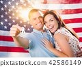 Military Couple Holds House Keys In Front of Flag 42586149