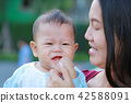 baby boy is sucking finger with Asian mother carry 42588091