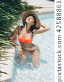 young attractive brunette woman under a palm tree 42588861