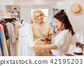 Dark-haired daughter with wavy hair hesitating about buying dress 42595203