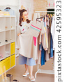 Fashion blogger standing near clothes rack in new showroom 42595323