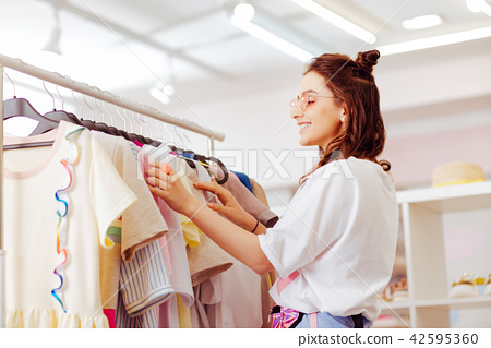 Beaming stylish businesswoman spending her weekend in showroom 42595360