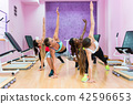 Fit women exercising with one arm on the floor during group class 42596653