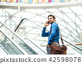A young businessman going up escalator, talking on the phone. Copy space. 42598078