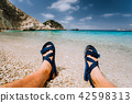 Young male feets wear blue flip-flop sandal sunbathing on sea beach with clear water 42598313