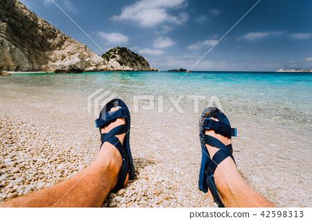 Young male feets wear blue flip-flop sandal sunbathing on sea beach with clear water 42598313
