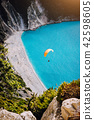 Myrtos Beach, Kefalonia Island, Greece. Figure of a parachutist skydiver with orange parachute 42598605
