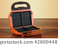 Opened waffle iron closeup on the wooden table 42600448