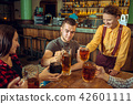 people, leisure, friendship and communication concept - happy friends drinking beer, talking and 42601111