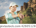 Portrait of a smiling young fitness girl in a cap and headphones checking her smart clock while 42605128