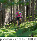 Active sporty woman riding mountain bike on forest trail . 42610039