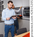 Man holding book with woman in background 42615205