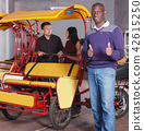 Smiling African-American pedicab driver standing near rickshaw cycle 42615250
