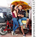Cheerful girl with boyfriend wanting to hire touristic trishaw for urban trip 42615337