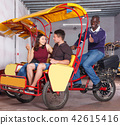 Glad tourist couple planning to hire velotaxi 42615416